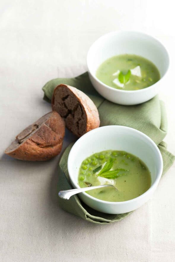 Pea, Edamame and Mint Soup on Table with Bread