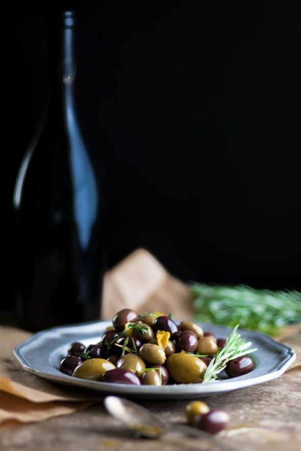 marinated olives next to wine bottle