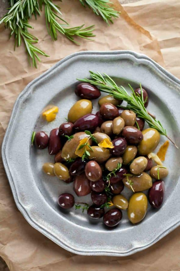 marinated olives with fresh herbs on platter