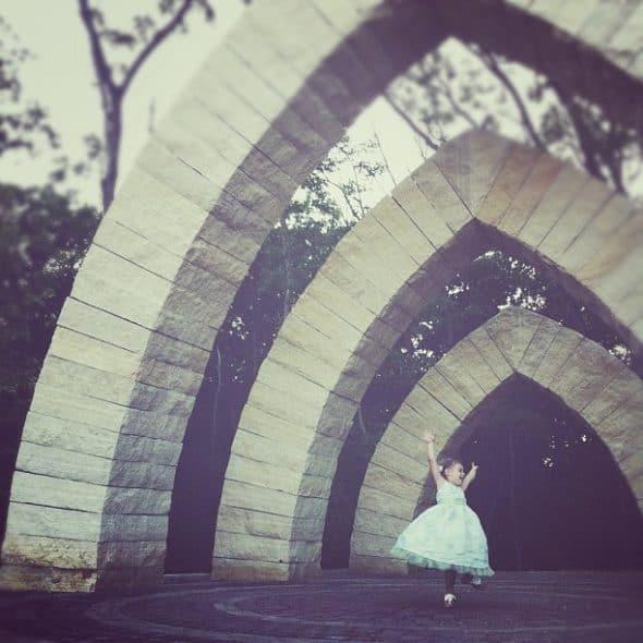 girl dancing under arch