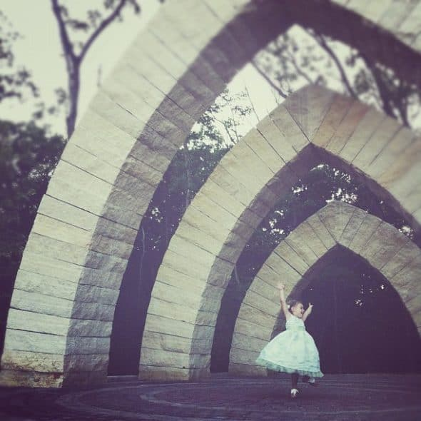 girl dancing under arch