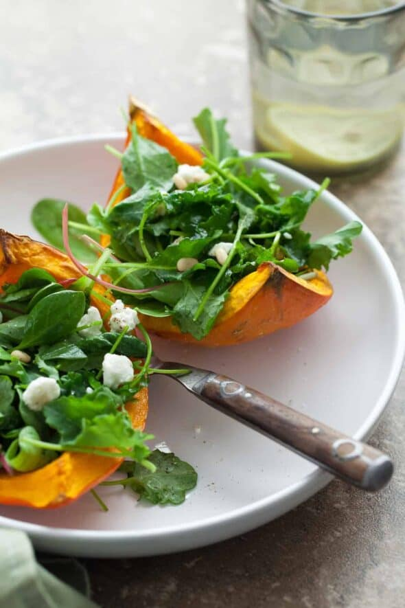 A mix of dark leafy greens are served on thick wedges of roasted squash and topped with goat cheese.