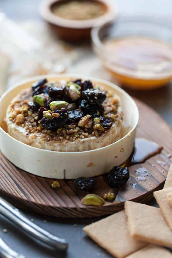 Baked brie is crusted in Dukkah then topped with chopped nuts and dried fruit.