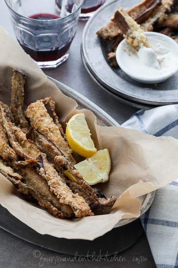 baked eggplant fries in basket with lemon wedges