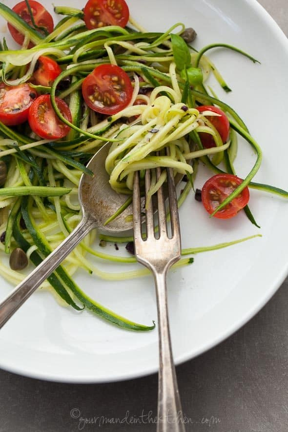 Zucchini Noodles with Caper Olive Sauce and Fresh Tomatoes on Plate with Fork