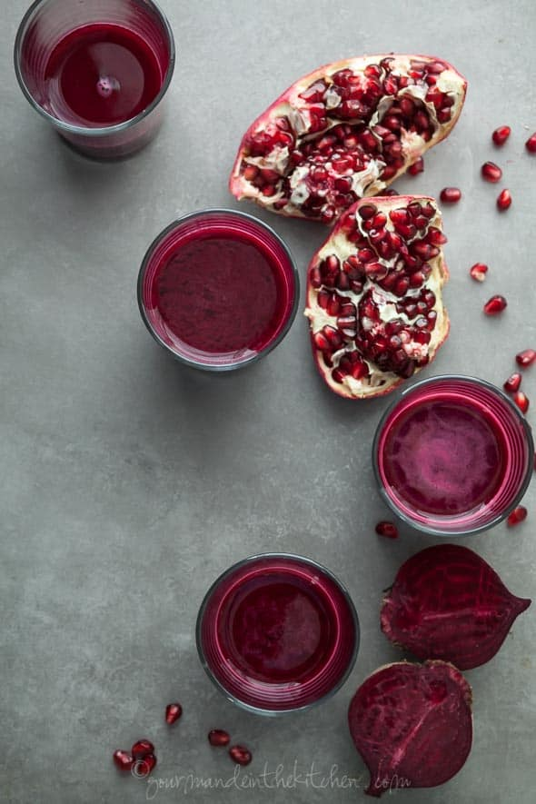Pomegranate, Beet, Red Cabbage Juice in Glasses Next to Split Pomegranate