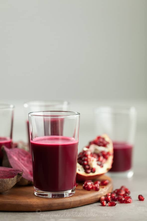 Pomegranate, Beet, Red Cabbage Juice in Glass on Wood Board