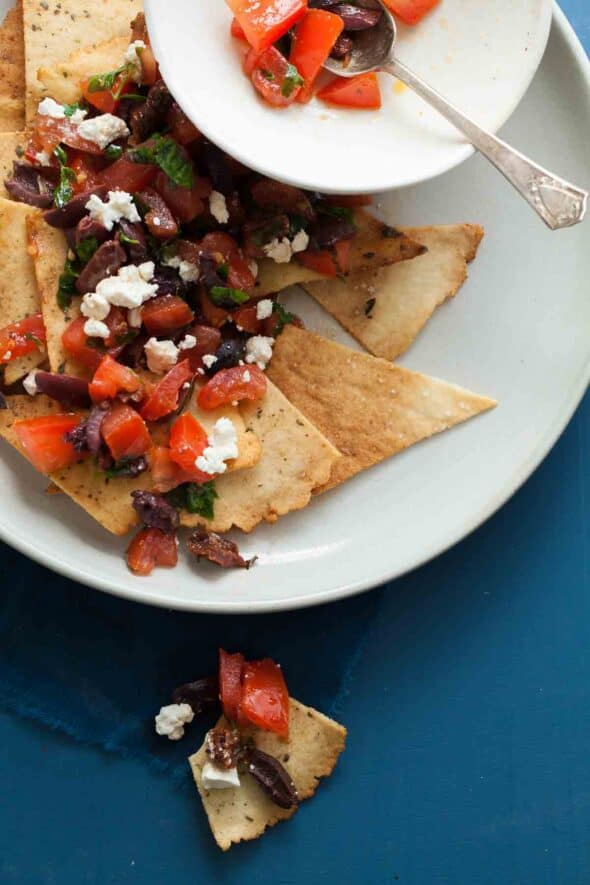 MEDITERRANEAN STYLE NACHOS WITH GRAIN-FREE PITA CHIPS Homemade grain-free pita triangles are topped with a chunky mix of tomatoes, olives and feta for a Mediterranean twist on nachos.
