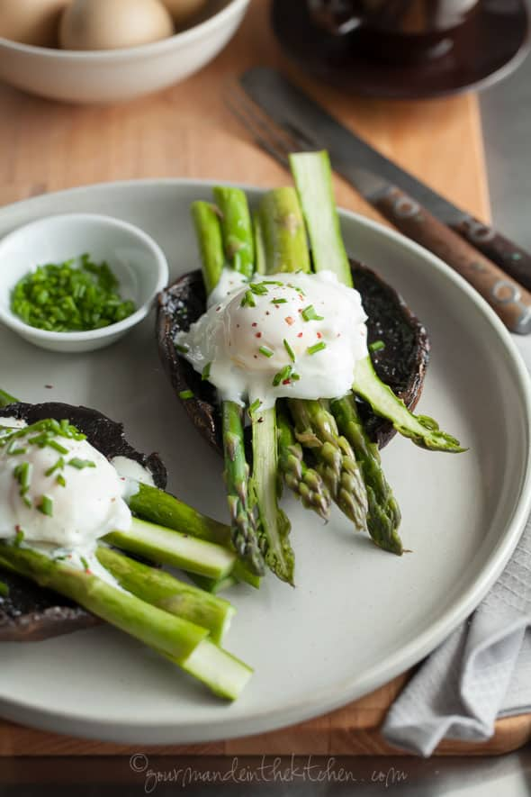 Portobello Mushroom Eggs Benedict with Asparagus with Goat Cheese Sauce on Plate Topped with Chives