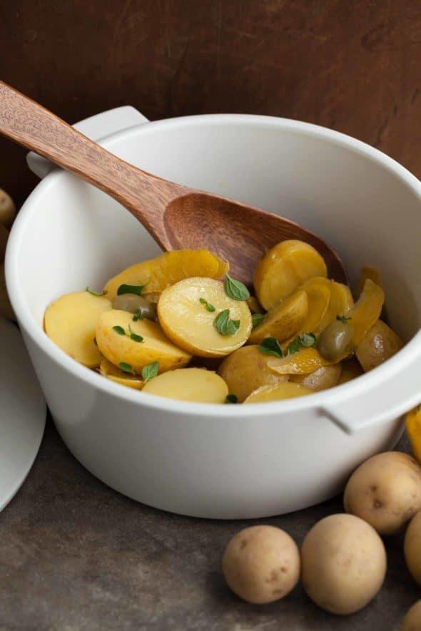 Greek Style Lemon Potatoes in Pot with Wooden Spoon