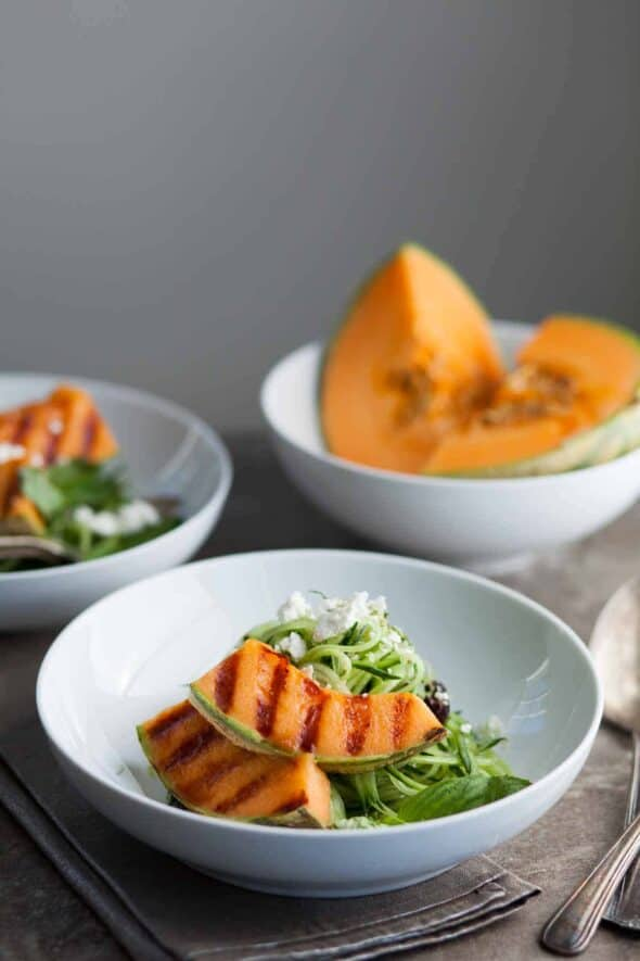 Fresh cucumber noodles are topped with sweet grilled cantaloupe wedges in this sweet and savory salad.