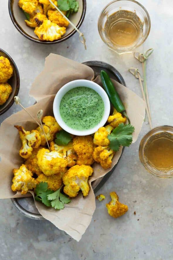 Turmeric Roasted Cauliflower Poppers with Cilantro Chutney in Bowls