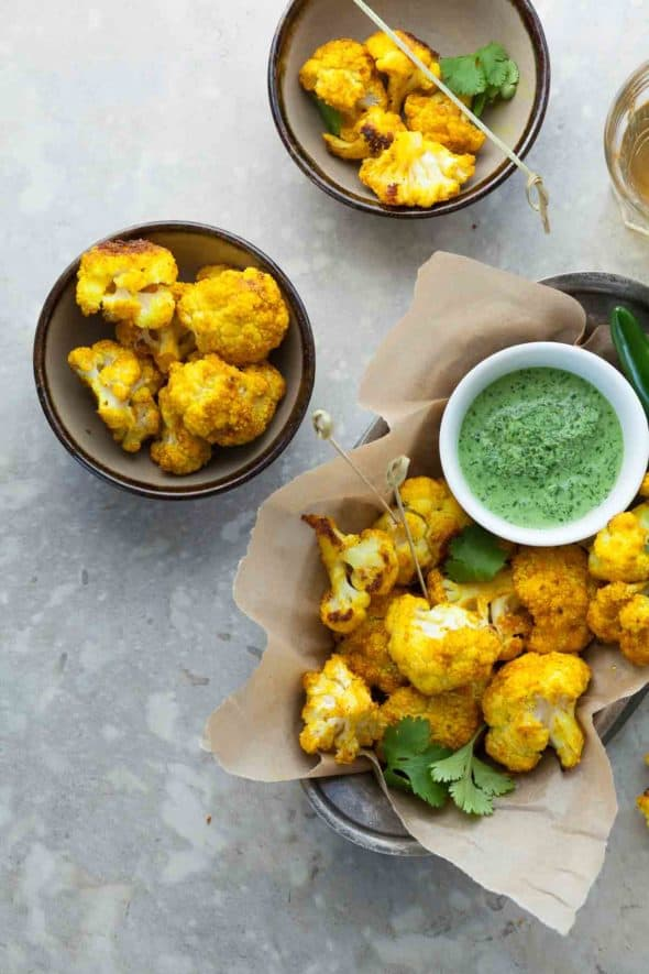Turmeric Roasted Cauliflower Poppers with Cilantro Chutney in Serving Bowls