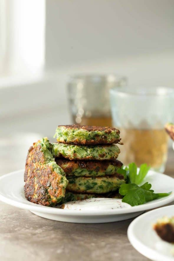 Broccoli Goat Cheese Fritters with Sumac Yogurt Stacked on Plate