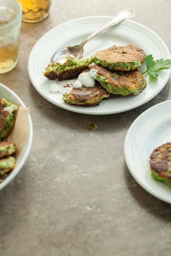 Gluten-Free Broccoli Fritters with Goat Cheese and Sumac Yogurt on Plates with Spoon