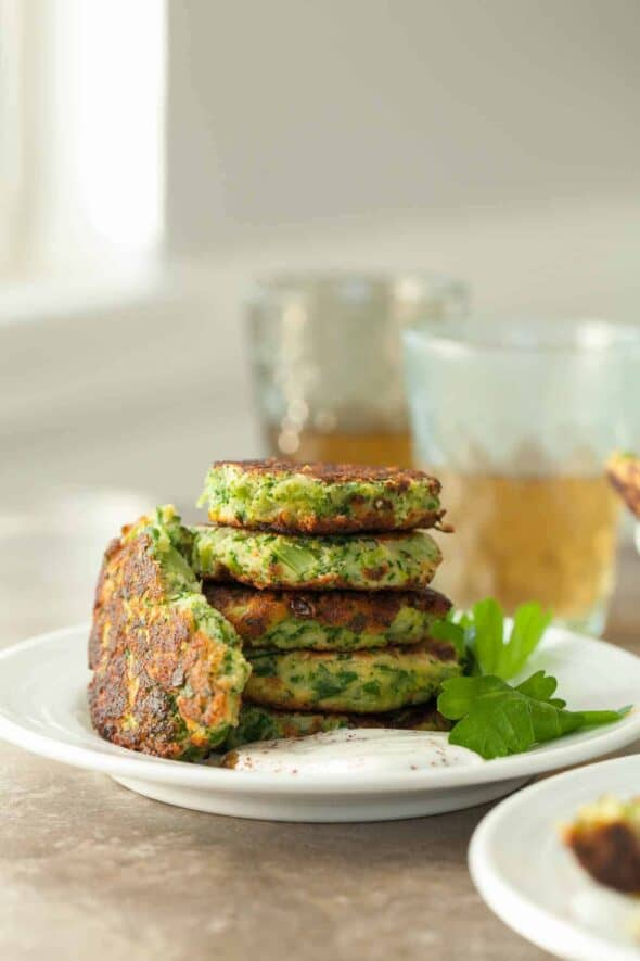 Gluten-Free Broccoli Fritters with Goat Cheese and Sumac Yogurt Stacked on Plate