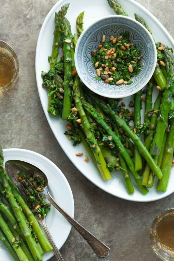 Asparagus with Caper Pine Nut Gremolata on Plates with Wine Glasses