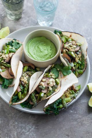 Mushroom Asparagus Tacos with Jalapeno Cashew Crema (Paleo, Vegan) - These paleo and vegan asparagus, mushroom and spinach filled tacos pack a flavorful punch thanks to a creamy jalapeno and cilantro crema.