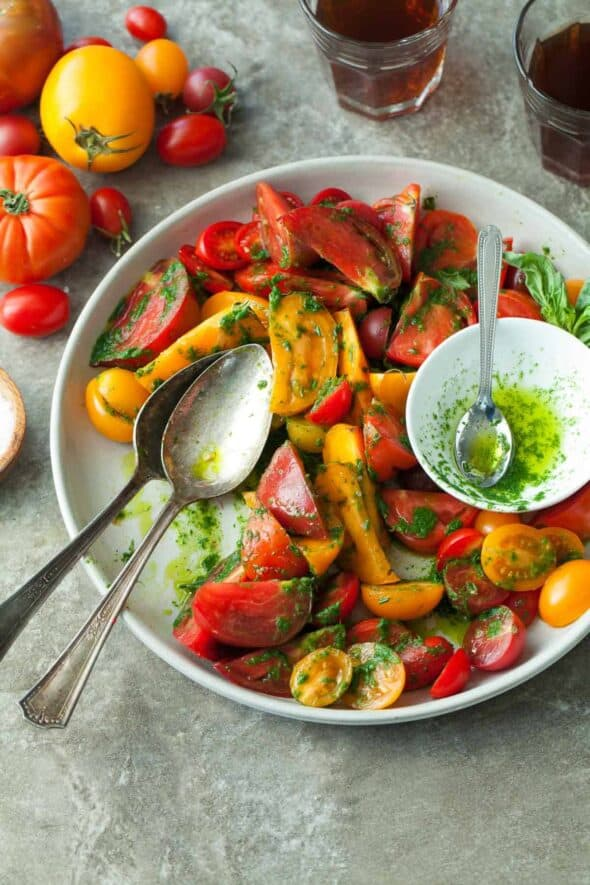 Heirloom Tomato Salad with Basil Parsley Oil on Plate with Serving Spoons
