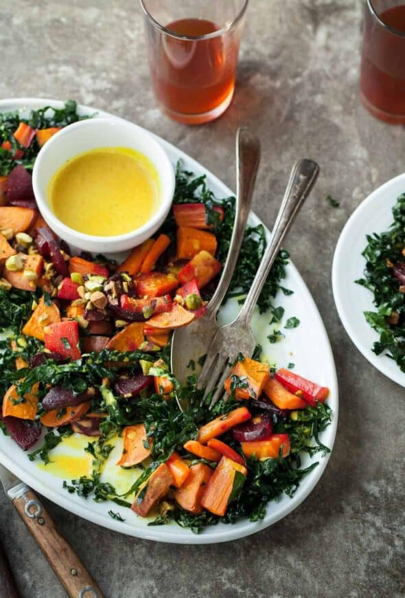 Roasted Root Vegetable and Kale Salad with Creamy Turmeric Dressing on Serving Plate with Spoon and Fork