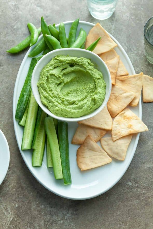 Spicy Green Almond Hummus on Serving Platter with Chips and Vegetables