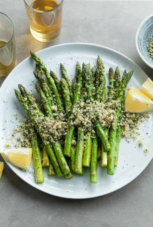 Grilled Lemon Poppy Seed Asparagus - Tender grilled asparagus is kicked up with the fresh flavors of lemon and a sprinkling of poppy seeds and macadamia nuts. #recipe #side #spring #summer #paleo #vegan #healthy