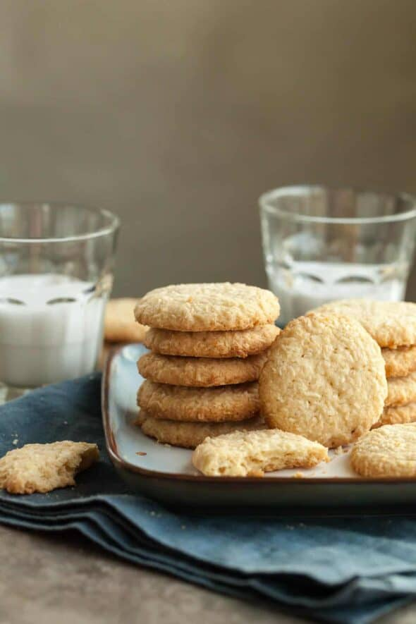 Crispy Gluten-Free Coconut Cookies Stacked on Plate