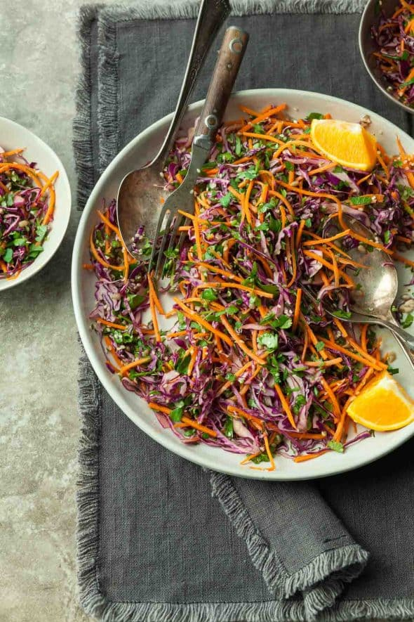 Carrot Cabbage Slaw with Orange Sesame Dressing (Vegan) - This simple Asian inspired carrot cabbage slaw is a crunchy and fresh addition to any summer meal. #sesame #orange #carrot #slaw #redcabbage #summerrecipes