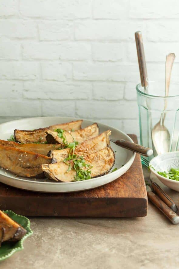 Tahini Miso Eggplant Wedges on plate with cutlery in glass