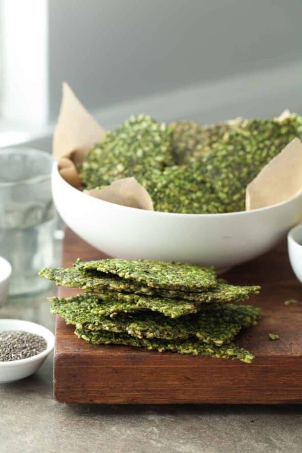 Gluten-Free Pesto Kale Seed Crackers in Stack Behind Bowl