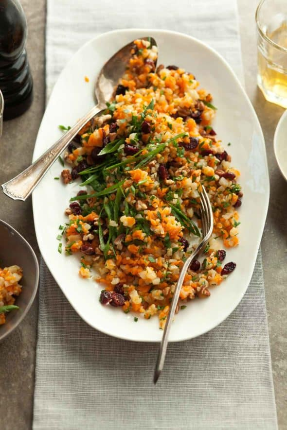 Carrot Cauliflower Rice Pilaf with Cranberries and Pecans in Serving Dish with Spoon and FOrk