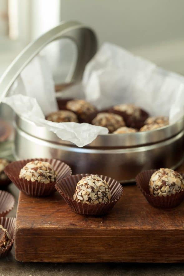 Chocolate Almond Fudge Truffles in small paper cups on wood board.